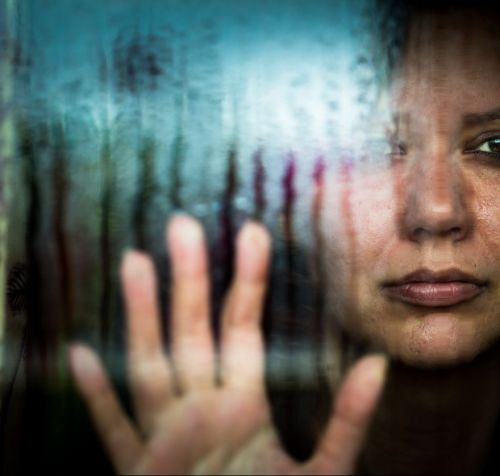 Depressed woman looking out of rainy window - Domestic violence concept